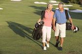 Couple de personnes âgées marchant le long du parcours de golf, sacs de transport — Photo