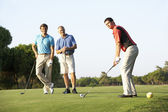 Group Of Male Golfers Teeing Off On Golf Course — Stok fotoğraf