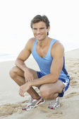 Young Man In Fitness Clothing Resting After Exercise On Beach — Stock Photo