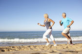 Senior koppel in fitness kleding loopt langs de strand — Stockfoto