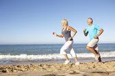Starszy para w odzież fitness, biegnącej wzdłuż plaży — Zdjęcie stockowe
