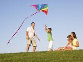 Unga familj, föräldrar med barn, spelar i ett fält — Stockfoto