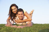 Young couple posing on a field — Stock Photo