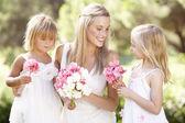 Bruid met de bruidsmeisjes buitenshuis op bruiloft — Stockfoto