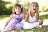 Two young girls posing in park — Stock Photo
