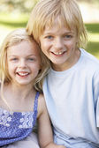 Brother and sister pose in a park — Stock Photo
