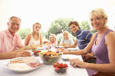 Extended family, parents, grandparents and children, eating outd — Stock Photo