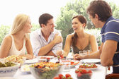 Two young couples eating outdoors — Stockfoto