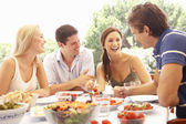 Two young couples eating outdoors — Stock Photo