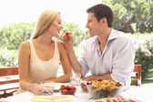 Young couple eating outdoors — Stock Photo