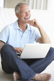 Senior man using laptop computer — Stock Photo