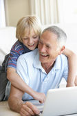 Senior man with young boy using laptop computer — Stockfoto