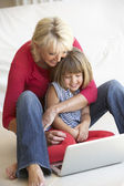 Middle age woman with young girl using laptop computer — Stock Photo