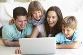 Padres jóvenes, con los niños, el ordenador portátil — Foto de Stock