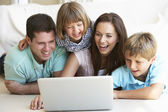 Young parents, with children, on laptop computer — Stock Photo