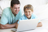 Jeune homme avec enfant sur ordinateur portable — Photo