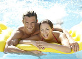 Young couple having fun in pool — Stock Photo