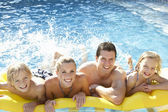 Familia joven divirtiéndose juntos en piscina — Foto de Stock