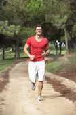 Young man running through park — Stock Photo