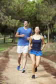 Young couple running in park — Stock Photo
