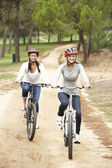 Couple riding bicycle in park — Stok fotoğraf
