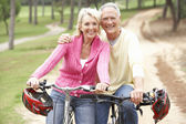 Senior couple riding bicycle in park — Stock Photo