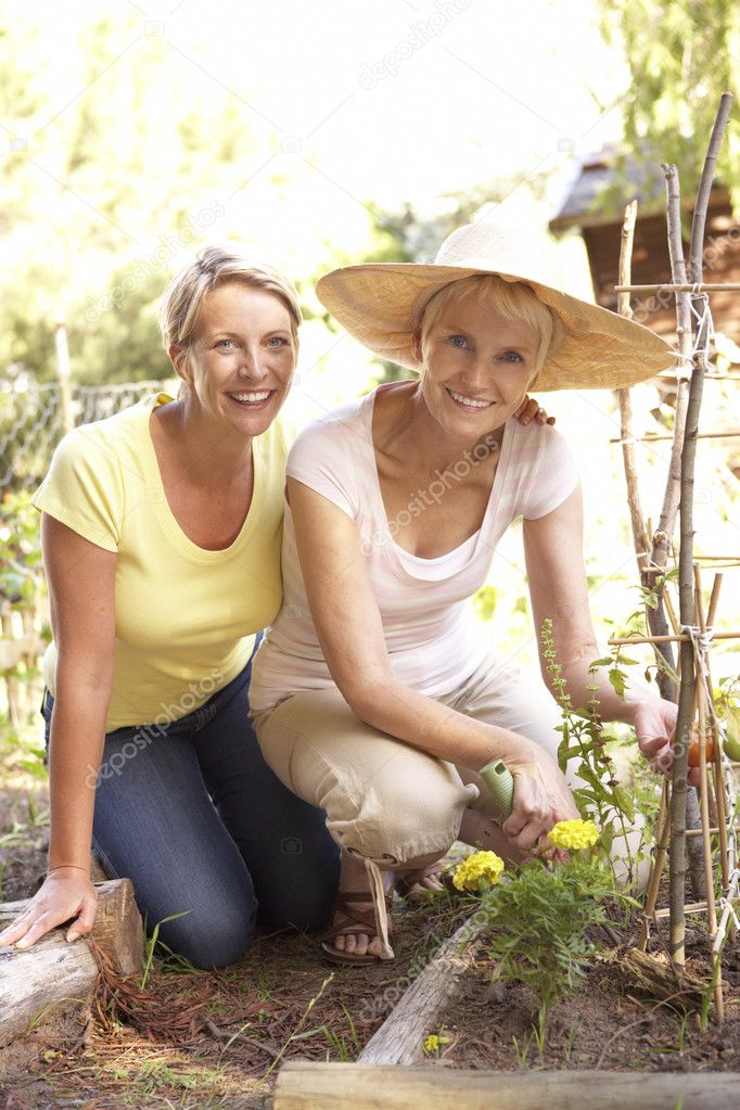 Senior Woman And Adult Daughter Relaxing In Garden  Lizenzfreies Foto #4840195