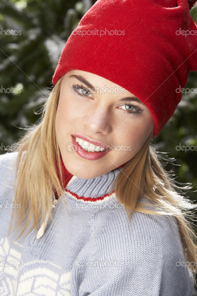 Fashionable Teenage Girl Wearing Cap And Knitwear In Studio In Front Of Christmas Tree — Stock Photo #4840668