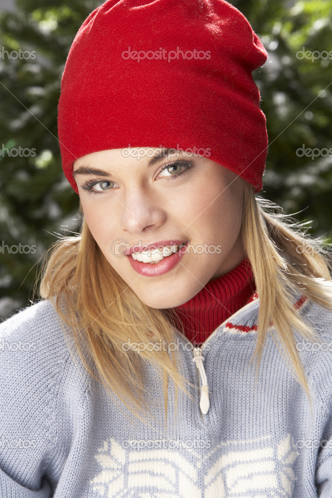 Fashionable Teenage Girl Wearing Cap And Knitwear In Studio In Front Of Christmas Tree — Stock Photo #4840672