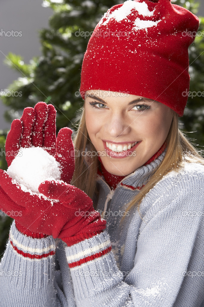 Fashionable Teenage Girl Wearing Cap And Knitwear Holding Snowball In Studio In Front Of Christmas Tree — Stock Photo #4840679