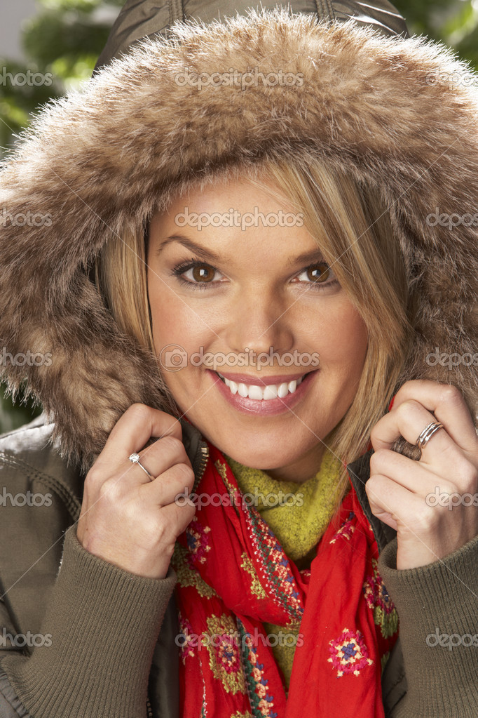 Fashionable Woman Wearing Parka Coat And Scarf In Studio In Front Of Christmas Tree  Stock Photo #4840689
