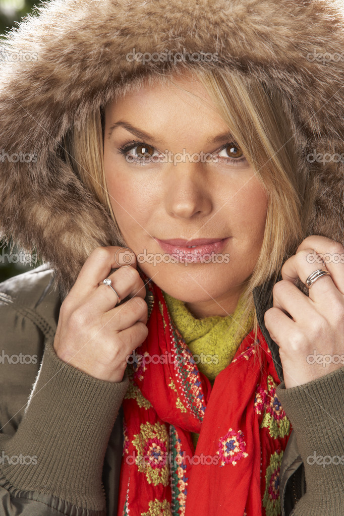 Fashionable Woman Wearing Parka Coat And Scarf In Studio In Front Of Christmas Tree  Stock Photo #4840690
