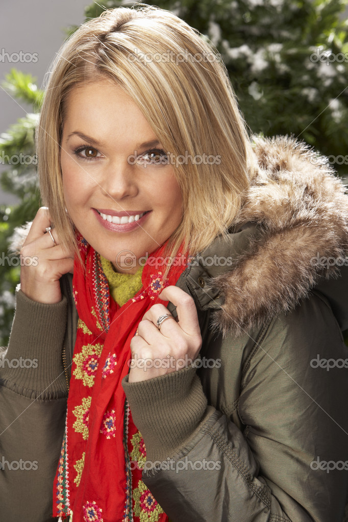 Fashionable Woman Wearing Parka Coat And Scarf In Studio In Front Of Christmas Tree — Stock Photo #4840695
