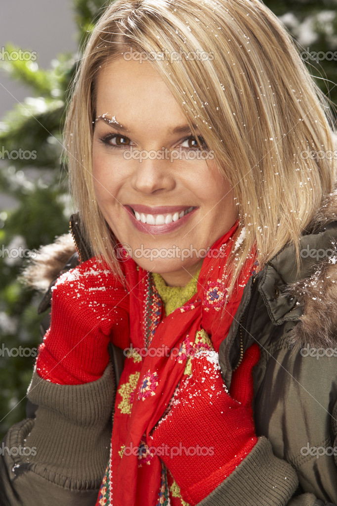 Fashionable Woman Wearing Parka Coat And Scarf In Studio In Front Of Christmas Tree — Stock Photo #4840698