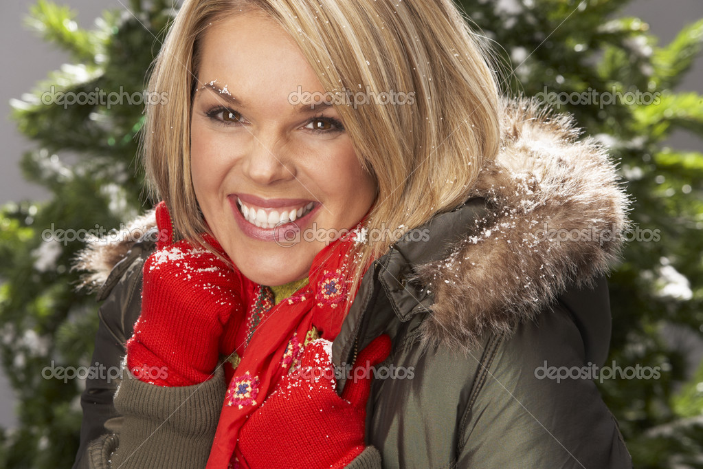 Fashionable Woman Wearing Parka Coat And Scarf In Studio In Front Of Christmas Tree — Stock Photo #4840706