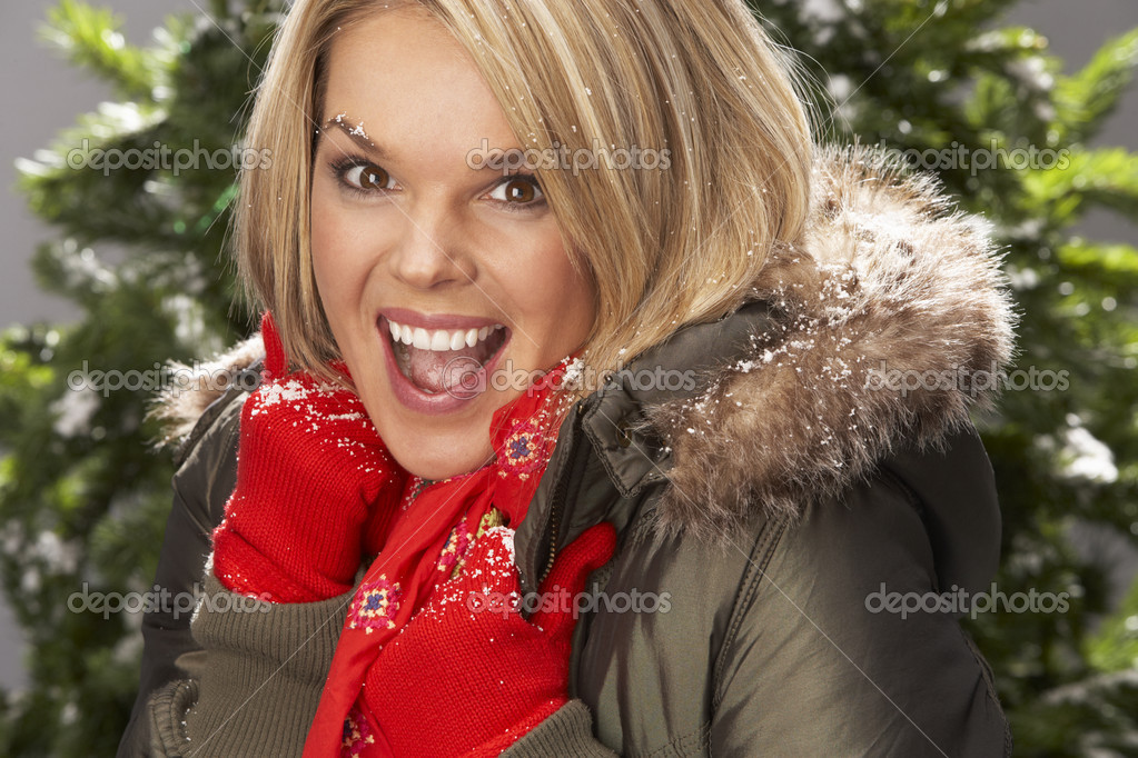 Fashionable Woman Wearing Parka Coat And Scarf In Studio In Front Of Christmas Tree — Stock Photo #4840710