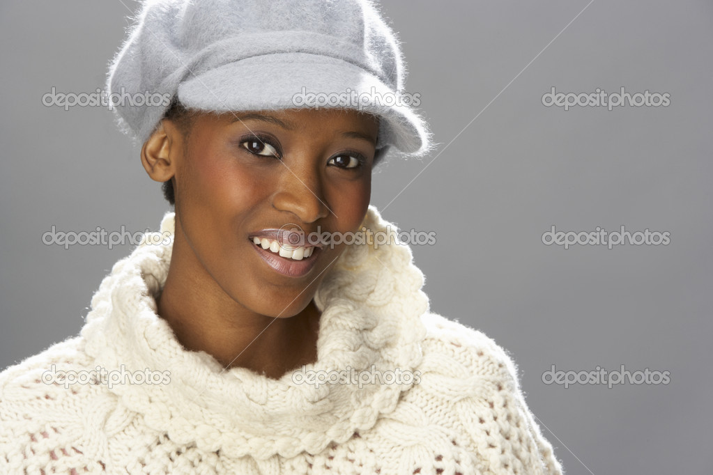 Fashionable Woman Wearing Knitwear And Cap In Studio In Front Of Christmas Tree — Stock Photo #4840728