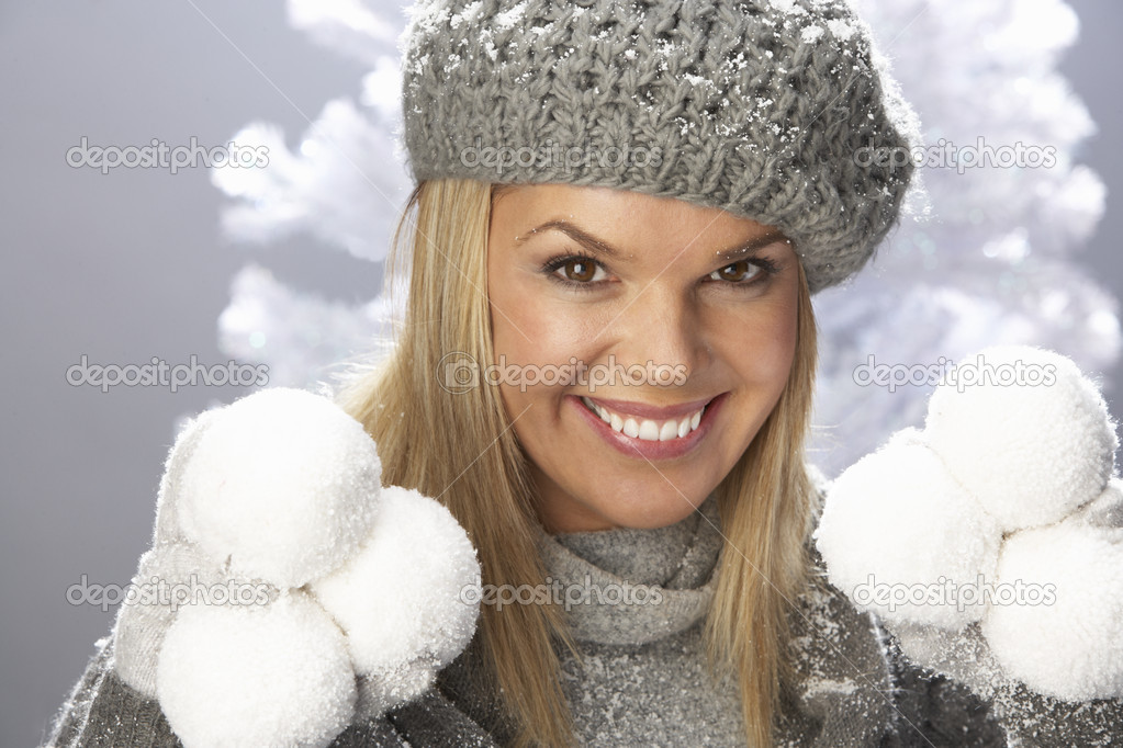 Fashionable Woman Wearing Cap And Knitwear Holding Snowball In Studio In Front Of Christmas Tree — Stock Photo #4840762