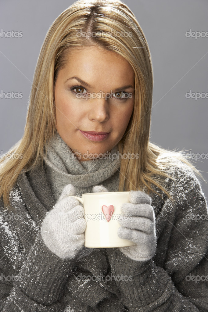 Young Woman Drinking Hot Drink Wearing Knitwear In Studio In Front Of Christmas Tree — Stock Photo #4840772