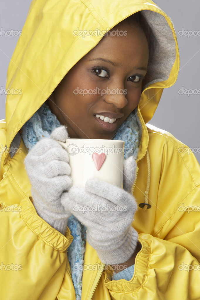Young Woman Drinking Hot Drink Wearing Yellow Raincaot — Stock Photo #4840777