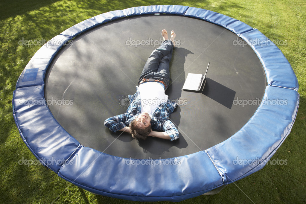 Young Man Relaxing On Trampoline With Laptop  Stock Photo #4840789