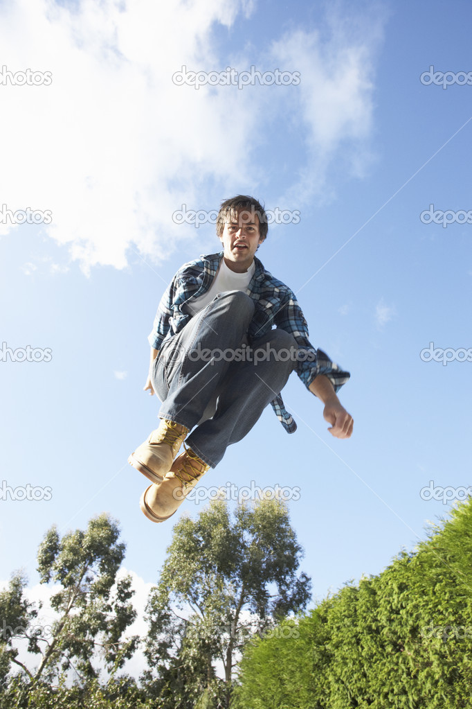 Young Man Jumping On Trampoline Caught In Mid Air — Stock Photo #4840796