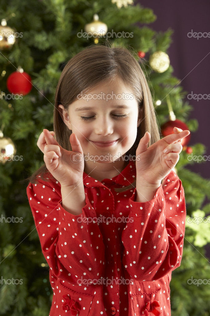 Young Girl Crossing Fingers In Front Of Christmas Tree — Lizenzfreies Foto #4840891