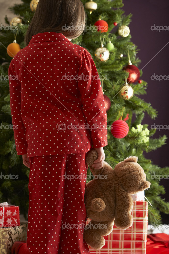 Oung Girl Standing With Teddy Bear In Front Of Christmas Tree — Lizenzfreies Foto #4840894