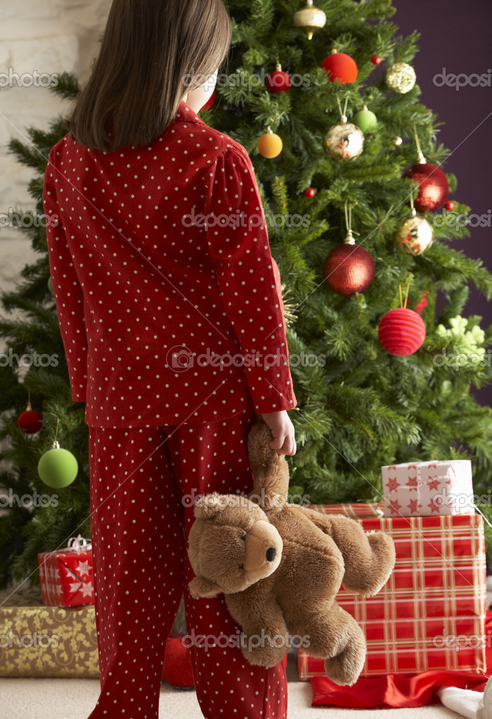 Oung Girl Standing With Teddy Bear In Front Of Christmas Tree — Stock fotografie #4840896