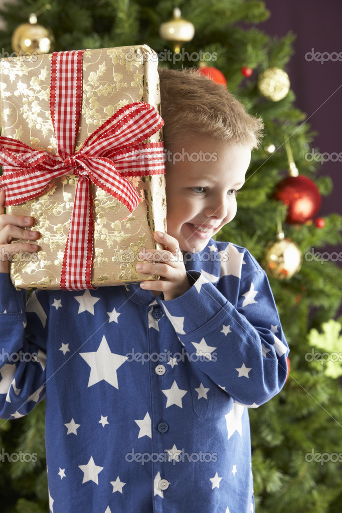 Boy with a giftbox in front of christmas tree  Stock Photo #4840904