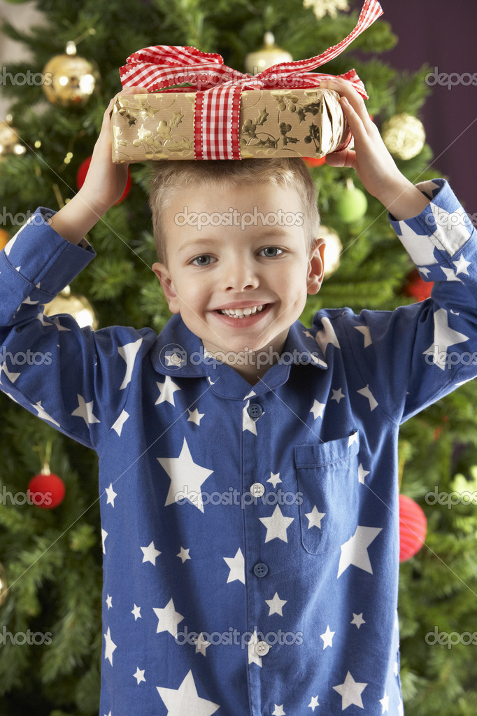 Boy eating cokie in front of christmas tree — Lizenzfreies Foto #4840905