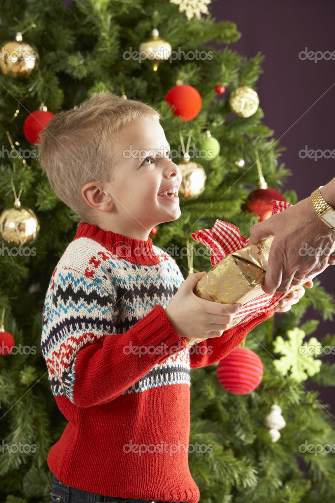 Young Boy Holding Christmas Present In Front Of Christmas Tree — Stock Photo #4840922