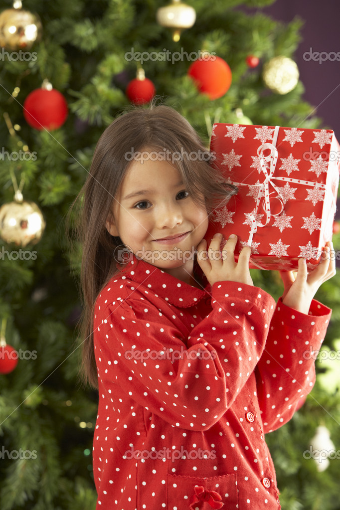 Young Girl Holding Gift In Front Of Christmas Tree — Stok fotoğraf #4840928