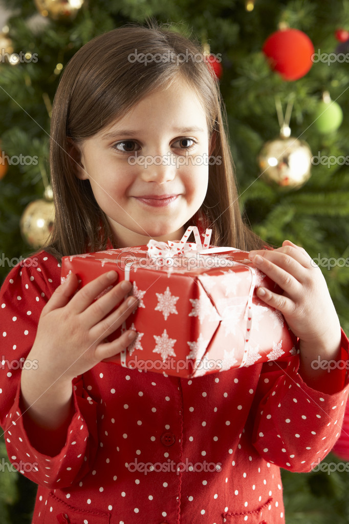 Young Girl Holding Gift In Front Of Christmas Tree — Foto Stock #4840981